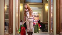 Young happy woman walking through the mall store with shopping bags. Stock Footage