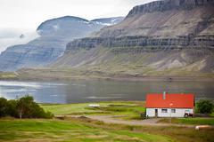 typical farm house at icelandic fjord coast - stock photo