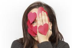 exasperated girl with face covered with paper hearts - stock photo