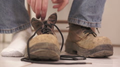 Stock Video Footage of Male Putting On Old Workboot