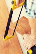 Stock Photo of close up of male hands cutting parquet floor board