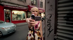 Woman points a vintage video camera  on the street in Chinatown Stock Footage