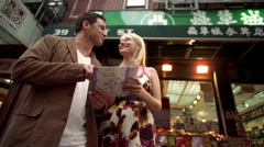Couple reading map for directions in Chinatown NYC Stock Footage