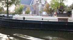 A very long boat house parked on the canal of Amsterdam - stock footage