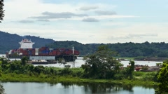 Cargo ship sailling through the Panama Canal with jungle and mountains Stock Footage