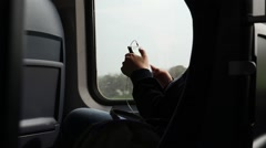 Passenger checking cell phone during a train ride Stock Footage