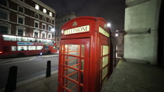 Red phone booth in London by night Stock Footage