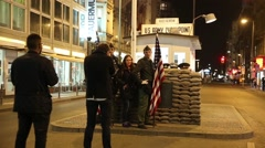 Tourist posing for picture with soldiers at Checkpoint Charlie Stock Footage