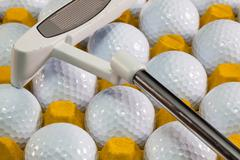 white golf balls in the yellow box and golf putter - stock photo