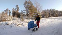 Mother walking with baby carriage in winter, 4K - stock footage