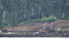 Construction activities in Panama Canal with backhoe and jungle in background Stock Footage
