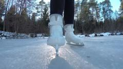 CLOSE UP: Ice skating on frozen pond in sunny forest - stock footage