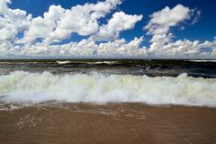 baltic wave and cumulus clouds - stock photo