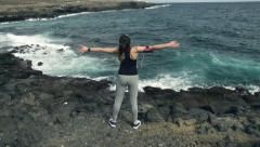 Woman standing on rocks by sea with wide open arms, slow motion HD Stock Footage