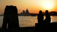 Young couple enjoying peacefulness of romantic sunset on the venetian lagoon Stock Footage