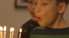 Young boy tries to blow out all the candles on his birthday cake Stock Footage