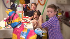 Boy hitting a pinata at party while his friends cheer him up in slow motion Stock Footage