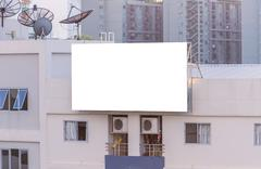 Blank billboard on building in city view background Stock Photos