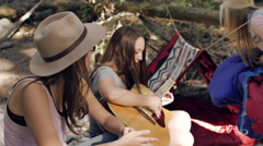 Young Woman Sets Up Her Sleeping Bag, Her Friends Play Guitar And Chat With Her Stock Footage