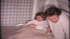 1624 - mom puts daughter to bed & reads her story - vintage film home movie Stock Footage