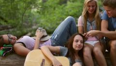 A Couple Braids Their Friend's Hair, The Friend Makes Faces (Dolly Shot) - stock footage