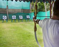 Archer man pulls the bowstring and arrow, aiming at a target Stock Photos