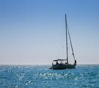 silhouette of solitary yacht without sails and with people on the horizon in  - stock photo