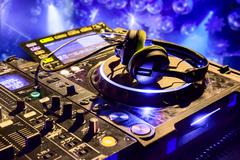 Dj mixer with headphones at nightclub.  in the background laser light show Stock Photos