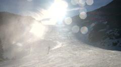Skier near a snow cannon making fresh powder snow. Mountain ski resort - stock footage