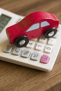 Red toy wooden car on calculator to illustrate cost of motoring Stock Photos