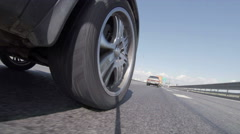 Vehicle wheel riding asphalt road, low angle action view. 4K - stock footage