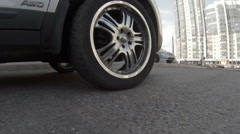 Car wheel riding through speed bump on asphalt road, low angle view Stock Footage