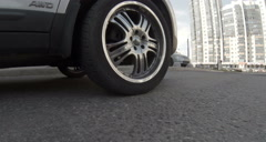 Car wheel passing through speed bump on asphalt road, low angle view Stock Footage