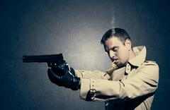 killer standing on dark background aiming before shooting - stock photo