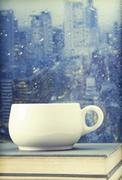 Stock Photo of coffee cup on a rainy day in front of the window