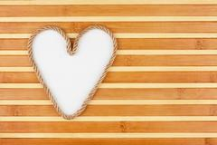 symbolic heart made of rope lying on a bamboo mat - stock photo