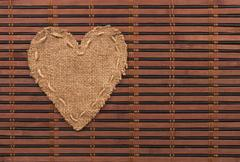 the symbolic heart of burlap lies on a bamboo mat - stock photo