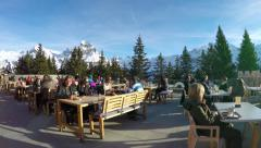 Ski tourists drinking and eating at the restaurant on mount over Engelberg Stock Footage