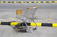 An abandoned shopping trolley on a parking place Stock Photos