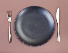 top view of black plate, fork, knife set on brown - stock photo