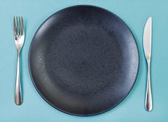 top view of black plate, fork, knife set on green - stock photo