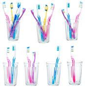 collection of tooth brushes in clear glases - stock photo