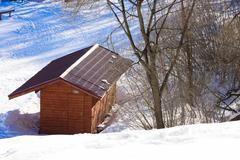 Small wooden lodge located in the snow in mountainous terrain. Stock Photos