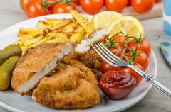 Big chicken schnitzel with homemade chilli french fries Stock Photos