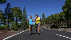 Sport fitness couple running playful having fun - Runner man and woman jogging Stock Footage