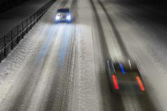 two cars on winter road - stock photo