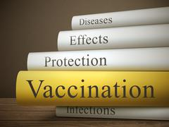 book title of vaccination isolated on a wooden table - stock illustration