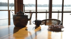 Old copper kettle ,teacup and basket with bagels are on big wooden table. - stock footage
