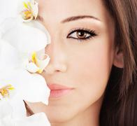 closeup on beautiful face with flowers - stock photo
