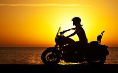 Woman biker over sunset Stock Photos